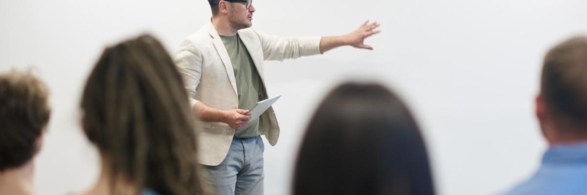 Man in beige blazer holding tablet computer 3184328